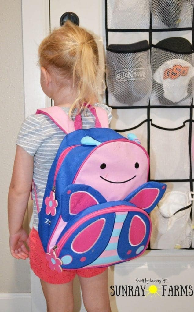 Toddler wearing a backpack ready to leave the house.