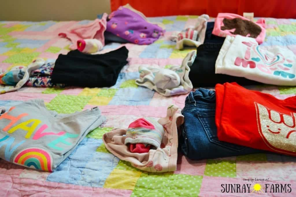 Children's outfits for the week laid out on a bed