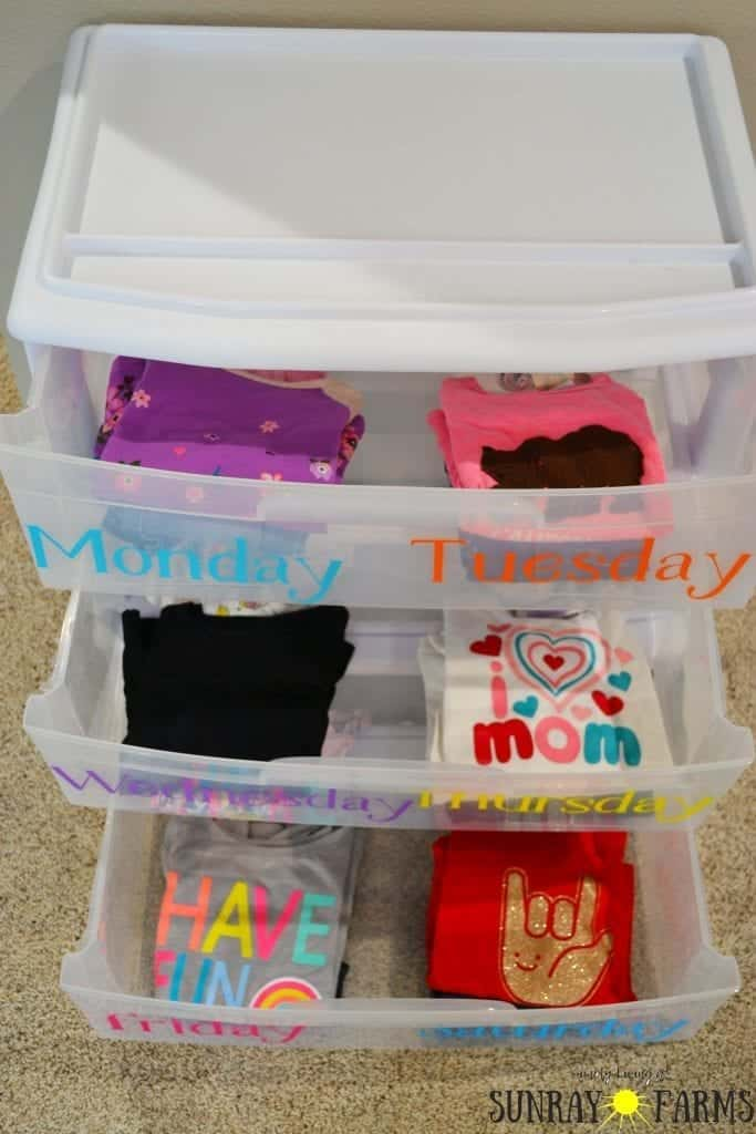 Children's outfits planned and organized by day of the week in a plastic drawer system.