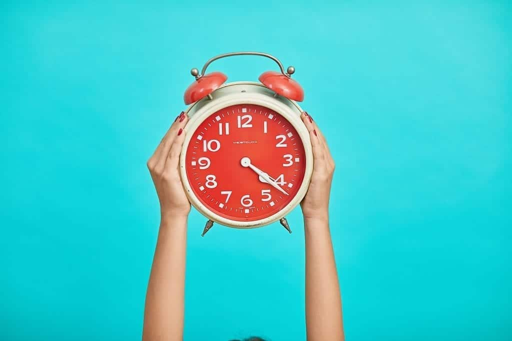 Hands holding a red and white analog alarm clock