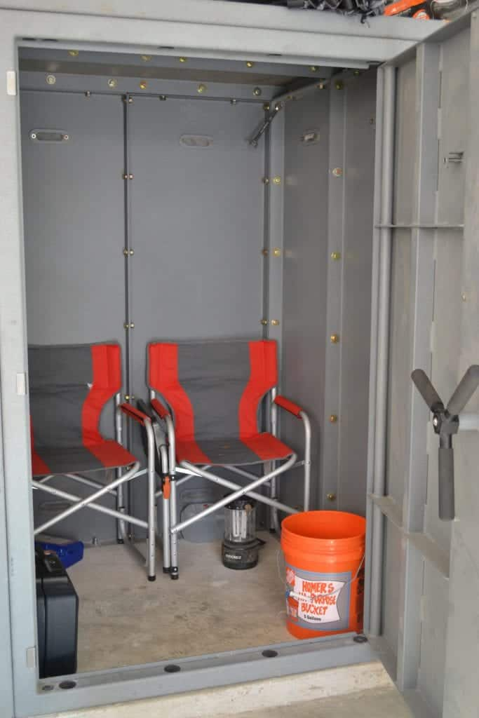 The inside of an Atlas Safe Room with folding chairs, a lantern, a first aid kit, and a fireproof safe.