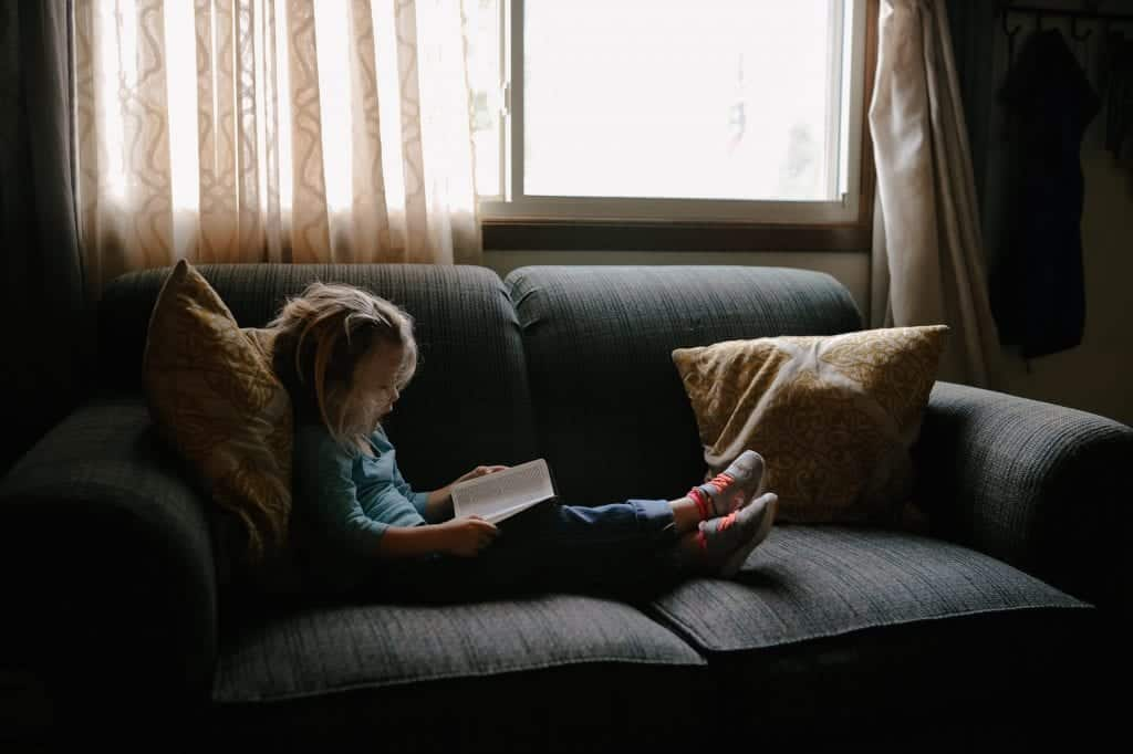 Little girl sitting on the couch reading a book